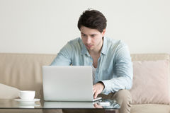Young man working at home office, using laptop computer, freelan Stock Photo