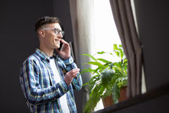 Young man working at home, standing by the window talking on phone. Concept of freelance work out of the office Stock Photography
