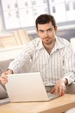 Young man working at home using laptop Stock Photo