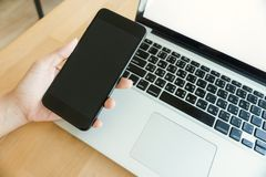 Young man working from home using smart phone mockup and laptop computer, man`s hands using smart phone in interior. Laptop and smartphone mockup. Closeup of Stock Image