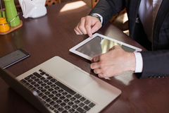 Young man working from home using smart phone and notebook compu Stock Image