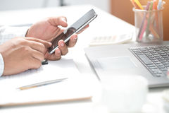 A young man working from home, using smart phones and notebook Royalty Free Stock Images