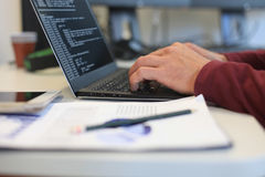 Young man working with laptop, business person at workplace. Stock Image