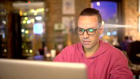 Young man working on laptop in city cafe. A young attractive hipster in a cafe, with a modern interior. The man works on. His stylish laptop. A designer or a stock footage