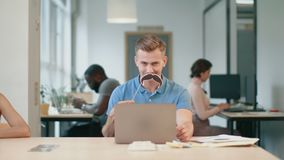 Young man working on laptop computer at coworking. Joyful man making male. With moustache symbol. Comic man having fun sitting with notebook at workplace stock video footage