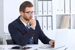Young man working with laptop computer, man`s hands on notebook, business person at workplace Stock Image