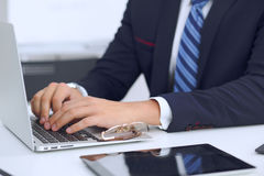Young man working with laptop computer, man`s hands on notebook, business person at workplace.  Royalty Free Stock Image