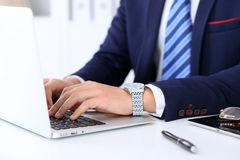 Young man working with laptop computer, man`s hands on notebook, business person at workplace Royalty Free Stock Photo