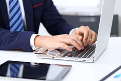 Young man working with laptop computer, man`s hands on notebook, business person at workplace.  Stock Photography