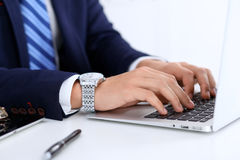 Young man working with laptop computer, man`s hands on notebook, business person at workplace.  Stock Photo
