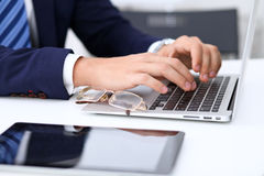 Young man working with laptop computer, man`s hands on notebook, business person at workplace.  Royalty Free Stock Photos