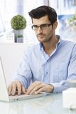 Young man working on laptop computer Stock Photography