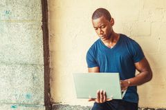 Young Man working on laptop computer. Young Handsome African American Man working on laptop computer outside, wearing blue V neck T shirt, standing against wall Stock Photography