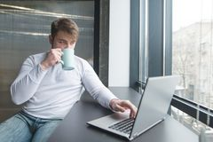 Young man working on a laptop in coworking and drinking coffee. A man drinks coffee while working in the office near the window Royalty Free Stock Photos