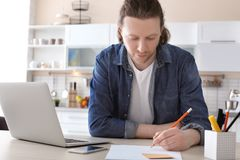 Young man working with laptop at desk. In home office Stock Images
