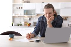 Young man working with laptop at desk. In home office Stock Photo
