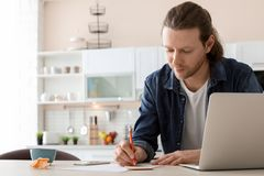 Young man working with laptop at desk in home. Office Stock Images