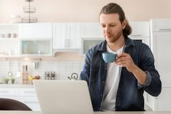 Young man working with laptop at desk in home. Office Stock Image