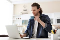 Young man working with laptop at desk. In home office Royalty Free Stock Photography