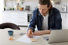 Young man working with laptop at desk. In home office Royalty Free Stock Image