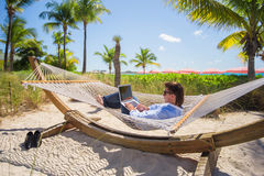 Young man working on laptop in hammock at tropical beach Royalty Free Stock Image