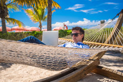 Young man working on laptop in hammock at tropical beach Stock Photography