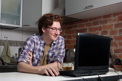Young man working on laptop. Happy guy is sitting in the kitchen and chatting with his friends Stock Image