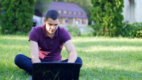 Young man working with a laptop on the lawn stock video