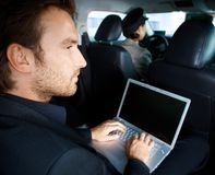 Young man working on laptop in limousine Stock Photos