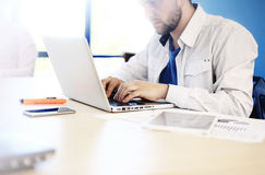 Young man working with laptop, man hands on notebook computer, business person at workplace Stock Image