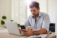 Young man working with laptop and mobile phone at his home offic Stock Photo