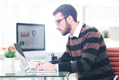 Young man working on laptop. Modern office. Business project Royalty Free Stock Photos
