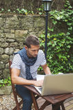 Young man working with laptop in outdoors. Attractive man working in your home garden Royalty Free Stock Photos