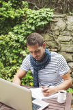 Young man working with laptop in outdoors. Attractive man working in your home garden Royalty Free Stock Image