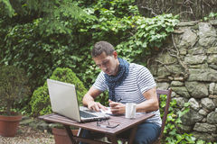 Young man working with laptop in outdoors. Attractive man working in your home garden Royalty Free Stock Photography