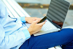 Young man working with laptop. Man's hands on notebook computer, business person in casual clothes in the street Royalty Free Stock Image