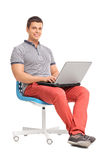 Young man working on a laptop seated on a chair stock images