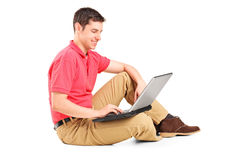 Young man working on laptop seated on the floor Royalty Free Stock Photography