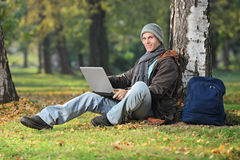 Young man working on laptop seated by a tree in pa Royalty Free Stock Photography