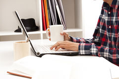 Young man working on laptop. Side view of young man in check shirt typing on laptop holding cup or tea or coffee, copy space in foreground Royalty Free Stock Photo