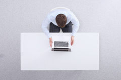 Young man  working on laptop, sitting  the desk in Royalty Free Stock Images