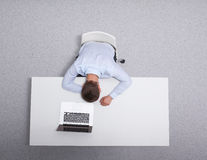 Young man working on laptop, sitting the desk in office Royalty Free Stock Photos