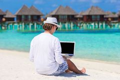 Young man working on laptop at tropical beach near Stock Images