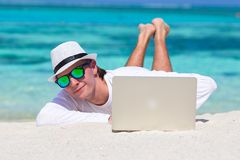 Young man working on laptop at tropical beach near Royalty Free Stock Photo