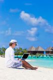 Young man working on laptop at tropical beach near Royalty Free Stock Photography