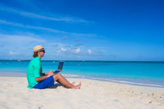 Young man working on laptop at tropical beach Royalty Free Stock Photos