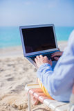 Young man working on laptop at tropical beach Stock Photography