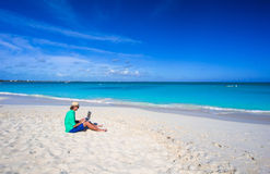 Young man working on laptop at tropical beach Stock Images