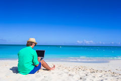 Young man working on laptop at tropical beach Royalty Free Stock Image