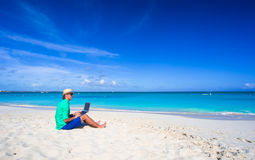 Young man working on laptop at tropical beach Royalty Free Stock Photo